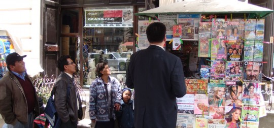 People reading the newspaper on a newsstand, a common sight in La Paz
