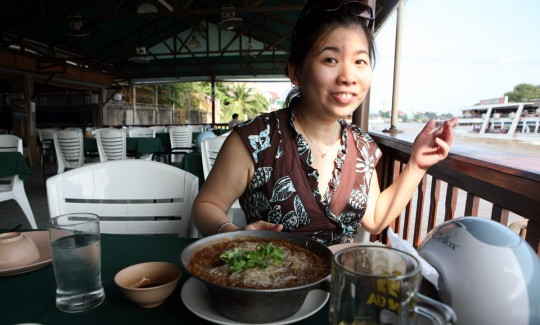 Kathryn is having food in a riverside restaurant.